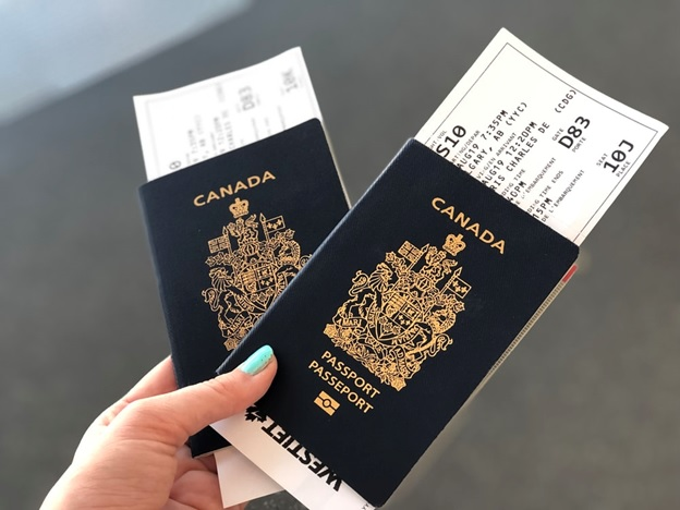 A woman holding two Canadian passports with boarding passes